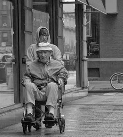 Older man in a wheelchair being pushed down the sidewalk by an older female.
